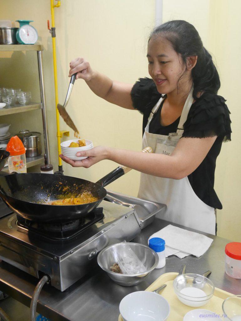 тайская девушка-повар сервирует жёлтый карри с курицей